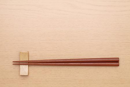 Chopsticks and chopsticks rest on table background