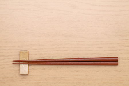 Chopsticks and chopsticks rest on table background
