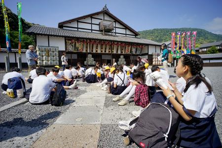KAGAWA, JAPONIA - 8 maja 2015: Wycieczka japońskiej szkoły podstawowej, Obserwacja ważnego historycznego budynku Kanamaruza w Kotohira, Kagawa w Japonii. Publikacyjne