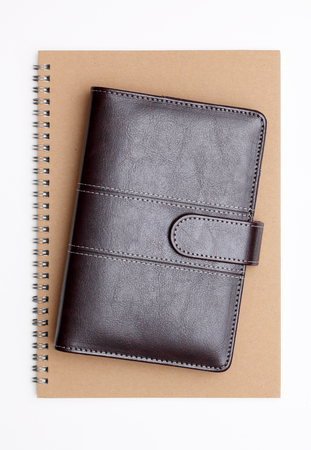 directory book: brown leather notebook and spiral notebook on white background