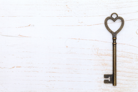 heart shaped vintage key on white wood background Stock Photo