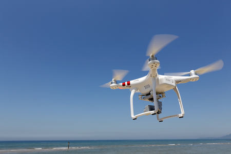 remote controlled: KAGAWA JAPAN - MAY 06, 2016: White remote controlled Drone Dji Phantom 3 equipped with high resolution video camera hovering in air with beach and the clear blue sky in the background