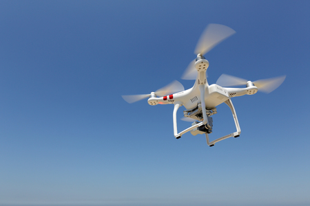 remote controlled: KAGAWA JAPAN - MAY 06, 2016: White remote controlled Drone Dji Phantom 3 equipped with high resolution video camera hovering in air and the clear blue sky in the background Editorial
