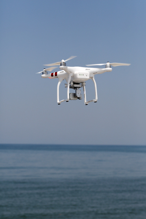 remote controlled: KAGAWA, JAPAN-MAY 20, 2016: White remote controlled Drone Dji Phantom 3 equipped with high resolution video camera hovering in air with beach and blue sky