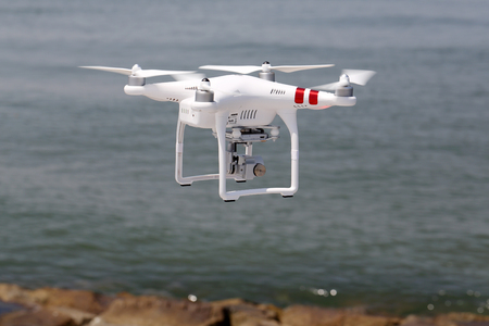 remote controlled: KAGAWA, JAPAN-MAY 20, 2016: White remote controlled Drone Dji Phantom 3 equipped with high resolution video camera hovering in air with beach