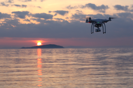 remote controlled: KAGAWA, JAPAN-MAY 30, 2016: Remote controlled drone Dji Phantom 3 equipped with high resolution video camera flying above the sea against a sunset sky. Editorial