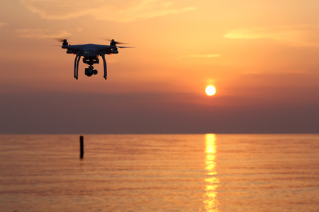 KAGAWA, JAPAN-MAY 31, 2016: Remote controlled drone Dji Phantom 3 equipped with high resolution video camera flying above the sea against a sunset sky.