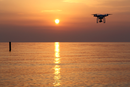 remote controlled: KAGAWA, JAPAN-MAY 31, 2016: Remote controlled drone Dji Phantom 3 equipped with high resolution video camera flying above the sea against a sunset sky.