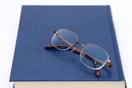 メガネと白い木製テーブルの上の本