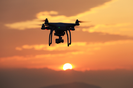 KAGAWA, JAPAN-JUNE 19, 2016: Remote controlled drone Dji Phantom 3 equipped with high resolution video camera hovering in air and sunset.