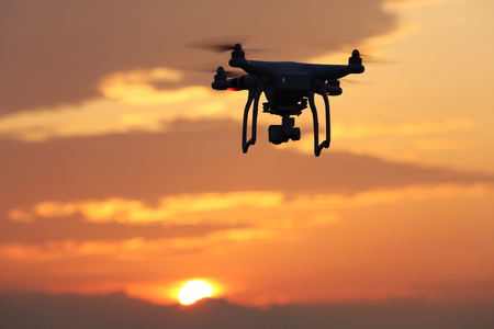 KAGAWA, JAPAN-JUNE 19, 2016: Remote controlled drone Dji Phantom 3 equipped with high resolution video camera hovering in air and sunset. Stock Photo