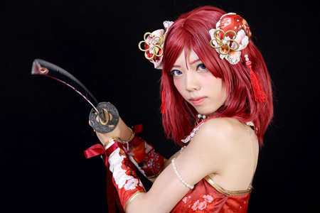 katana sword: Young asian girl dressed in cosplay costume with katana sword on black background
