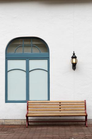 retro: outdoor bench with white wall on brick street Stock Photo