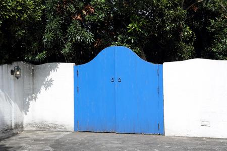 Gesloten houten hek met witte gips muur