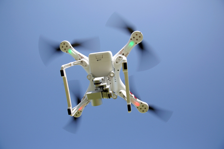 remote controlled: KAGAWA, JAPAN-OCTOBER 24, 2016: White remote controlled Drone Dji Phantom 3 equipped with high resolution video camera hovering in air and the clear blue sky in the background Editorial
