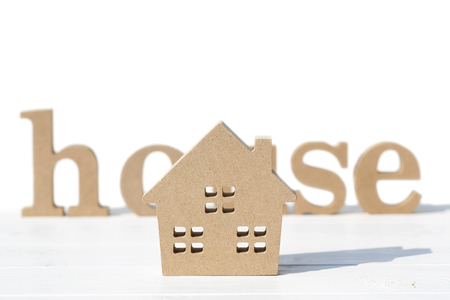 Wooden toy house and word on table, on white background