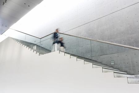 bajando escaleras: Blurred motion of women moving down stairs Foto de archivo