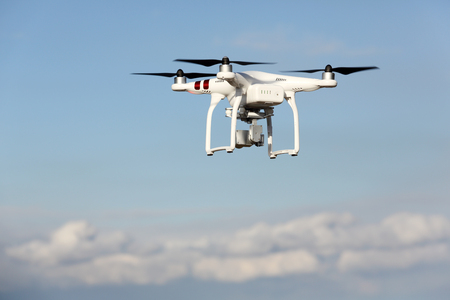 remote controlled: Kagawa Japan - December 15, 2016: White remote controlled Drone Dji Phantom 3 equipped with high resolution video camera hovering in air with shore and blue sky