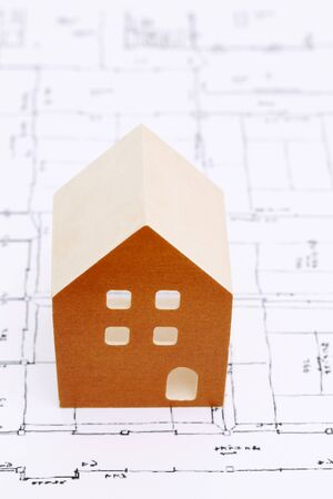 Wooden model of house on blueprints, construction plan Stock Photo