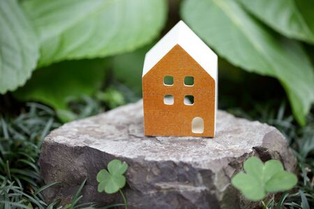 toy house: Wooden toy house on stone, green background