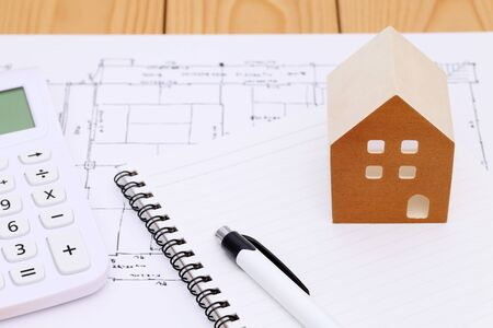 Wooden model of house and blueprints, construction plan Stock Photo