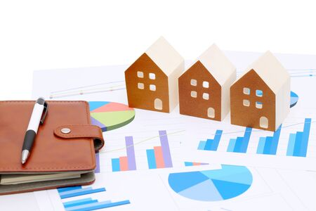 57: Miniature model of house on the chart printed documents, leather notebook and pen Stock Photo