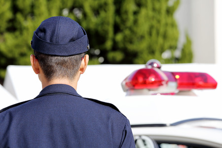 Back view of Japanese police officers with patrol car