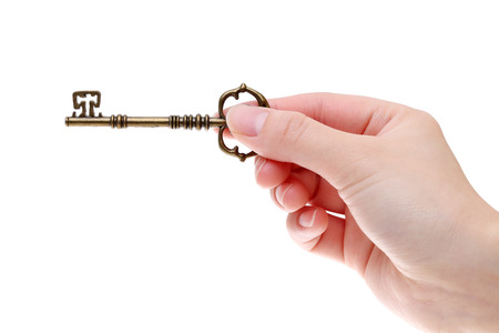 白い背景に分離されたアンティークの鍵を持っている手
