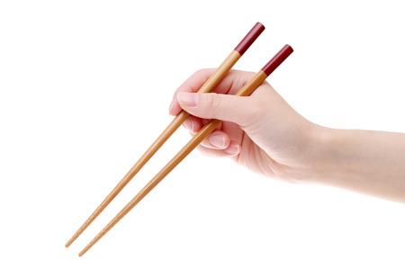 Hand die houten eetstokjes houdt die op witte achtergrond worden geïsoleerd Stockfoto