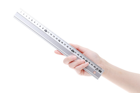 Hand holding metal ruler. Stock Photo