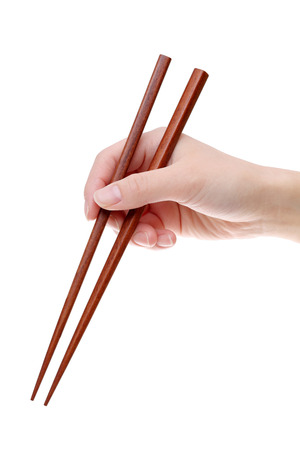 Hand holding wooden chopsticks on white background