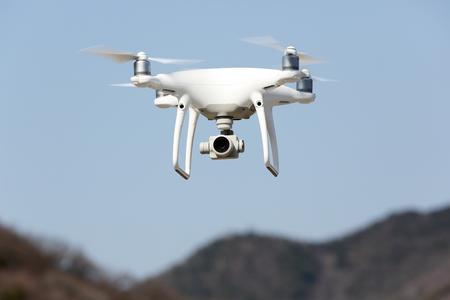 Witte hommel quadcopter met het vliegen in de blauwe hemel