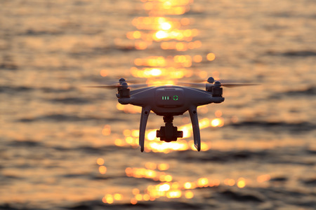 White drone quad copter flying in air and sparkle sunlight on sea