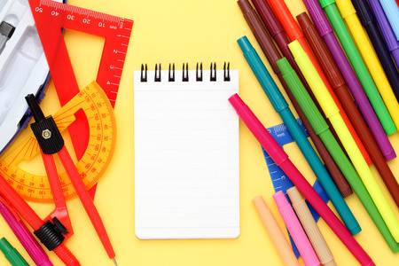 diameter: Multicolored pen, rulers and notebook on yellow background