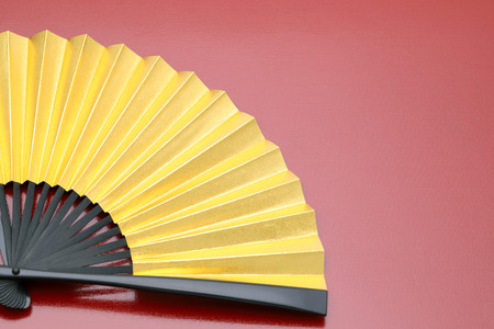 traditional chinese style golden hand fan on red background