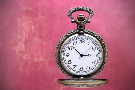 old pocket watch on grunge red wall background Stock Photo