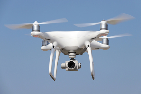 spyware: White drone quad copter with flying in the blue sky