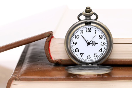Old pocket watch with old books on white background