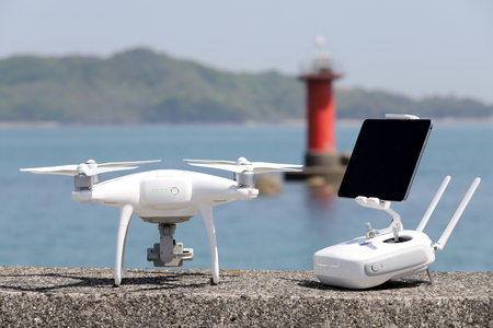 drone and remote controller with monitor on concrete jetty