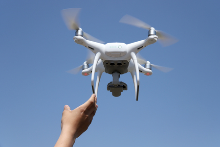 Hand catching drone aircraft in blue sky background, camera operator concept of aerial photography