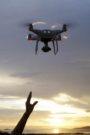 Hand catching drone aircraft in sunset sky background