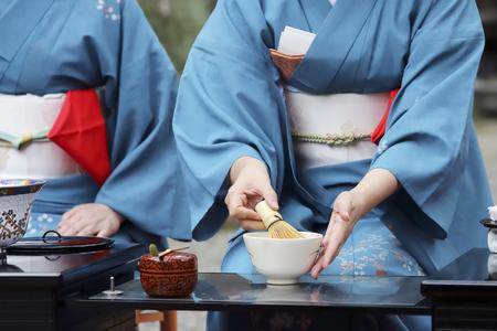 Donna giapponese in kimono tradizionale che prepara la cerimonia del tè verde giapponese al giardino