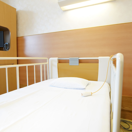 Room with empty bed and medical equipment Stock Photo