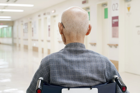 Back view of old man sitting on wheelchair in hospital hallway