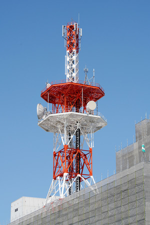 View of communication tower with antenna against blue sky