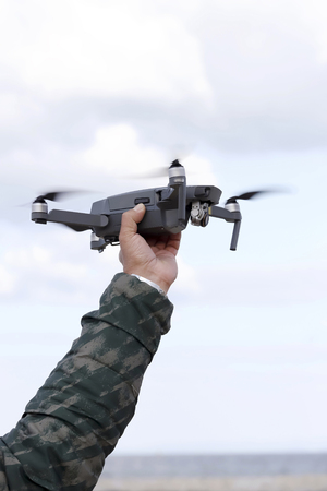 Hand catching drone aircraft in sky background, camera operator concept 写真素材