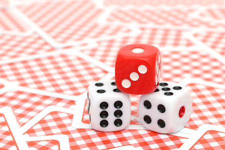 Red dice on playing cards background