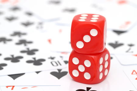 red dice with playing cards are on the background