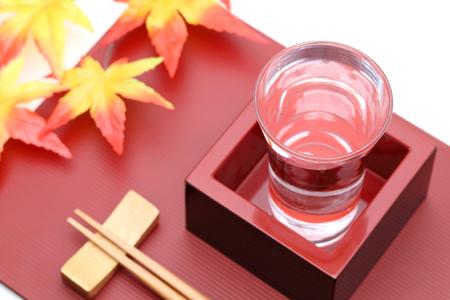 Japanese wooden box masu with sake on wooden tray