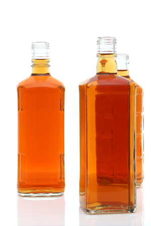 Glass bottle of whiskey on a white background
